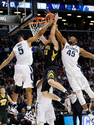 Villanova guard Phil Booth (5) and Villanova forward Darryl Reynolds (45) defend Iowa forward Nicholas Baer (51) during the first half of a second round NCAA men's college basketball game in the NCAA tournament, Sunday, March 20, 2016, in New York. (AP Photo/Kathy Willens)