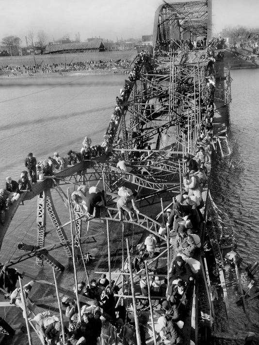 FILE - In this Dec. 4, 1950 file photo, residents from Pyongyang, North Korea, and refugees from other areas crawl perilously over shattered girders of the city's bridge as they flee south across the Taedong River to escape the advance of Chinese Communist troops. Sports ties between the rival Koreas often mirror their rocky political ties. (AP Photo/Max Desfor, File)