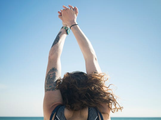 Gretchen Matt stretches her arms on the beach near Fort Pickens on Friday, March 3, 2017, after having completed her 1,100-mile hike in 40 days.