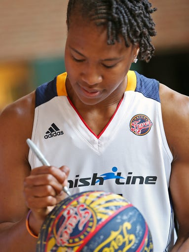 Indiana Fever forward Tamika Catchings autographs a