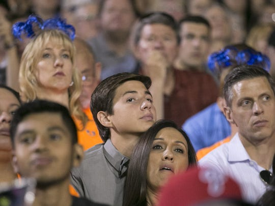 Stephen Dwyer, (center) student body president and member of the Class of 2016 of Dobson High School, rests his chin on the head of his mother, Trish Dwyer, next to his father, Rick Dwyer, (right) while sitting in the bleachers during the Dobson High graduation at the Mesa high school on Thursday evening, May 26, 2016. Dwyer had to miss his junior year while undergoing treatment for leukemia. He was several credits short and  was not allowed to sit with his class in cap and gown, which he had requested. He had to sit in the bleachers after leading the students in.
