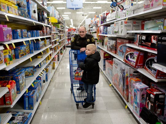 St. Clair County Sheriff's Deputy Ryan Kacafirek pushes Adrian Mowrer, 7, of Fort Gratiot, through an isle during Shop with a Cop Tuesday, Dec. 15, 2015 at Meijer in Fort Gratiot.