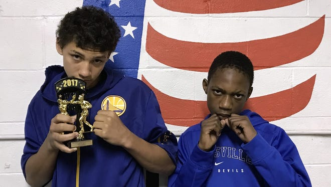 Jamall Norris, left, and Robert Guest, of the Zanesville Police Athletic League, pose after Norris' win last Saturday at the Chesapeake Community Center.