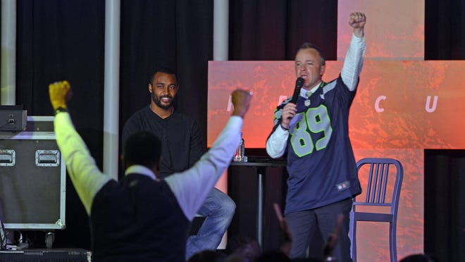 Lead pastor Tim Payne preaches to his Momentum Church congregation as Seattle Seahawks' receiver Doug Baldwin looks on Easter Sunday at Gulf Breeze Elementary School Auditorium.