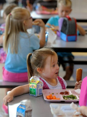 Kennedy Krell vistis with fellow kindergartners during lunch on the first day of school at Baltic Elementary School on Wednesday. School lunch prices in Baltic have gone up 40 cents since 2010.