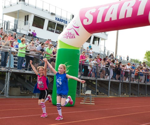 Gabrielle Patton, left, and Allyson Jenkins, right, of Verona Elementary hold hands as they cross the finish line at the annual Girls on the Run 5K at Harper Creek on Friday evening.