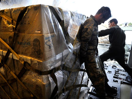 Staff Sgt. Charles Brown (left) and Senior Airman Ryan Bayles push a pallet away from the door and toward the rear of a U.S. Air Force KC-10 cargo plane Firday at Dyess Air Force Base. Seven pallets carrying more than 300,000 meals were loaded aboard the aircraft. The food is bound for refugee camps in northern Iraq.