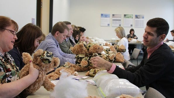 """Curt Weinstein, right, vice president and general manager at Corning Inc.'s Advanced Optics Specialty Materials, was among those who recently helped make """"Battalion Buddy"""" teddy bears."""