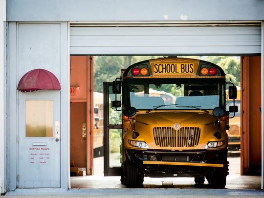 Muncie Community School buses are parked at the Auxilio