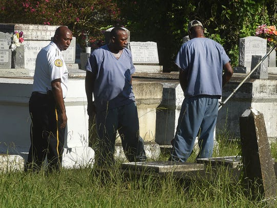 Opelousas Police Chief Donald Thompson watches as trusties from the Opelousas City Jail cut  grass inside Myrtle Grove Cemetery.