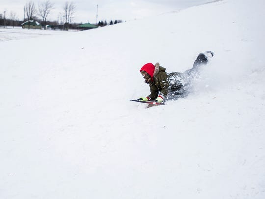 Luke Riehl, 7, rides his sled down the hill in the