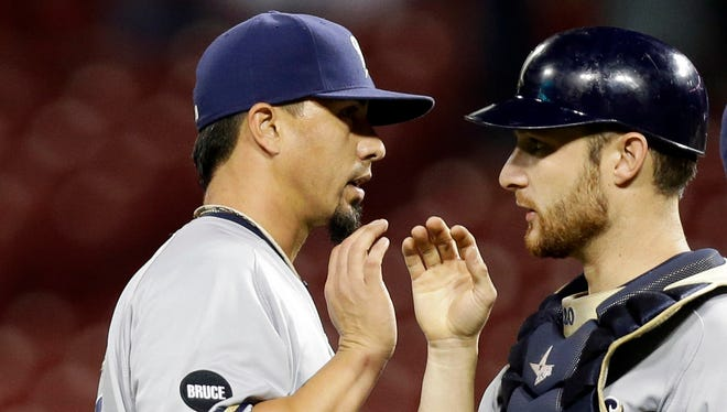 Milwaukee Brewers pitcher Kyle Lohse, left, high-fives catcher Jonathan Lucroy, center, after a game last September. The Brewers are dealing with a rash of pink eye that has broken out in the clubhouse and are staying away from the usual high-fives in the dugout.
