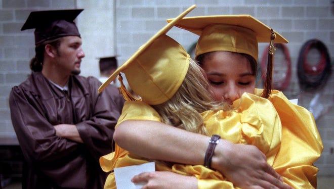 Holt High School graduate Liz Perez hugs classmate Billie Poufcas prior to the commencement ceremony held at the Jack Breslin Student Events Center, June 8, 1997.