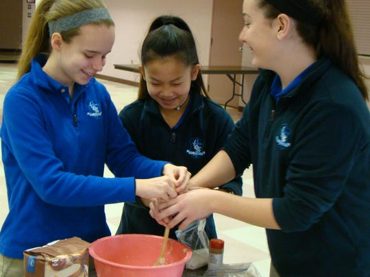 Sam Arnold, Olivia Reckner, and Raele Ruschman (left to right) use teamwork as they mix the ingredients for their bread dough. The eighth-grade students at St. Joseph, Cold Spring are making bread to see the reaction of yeast and sugar.