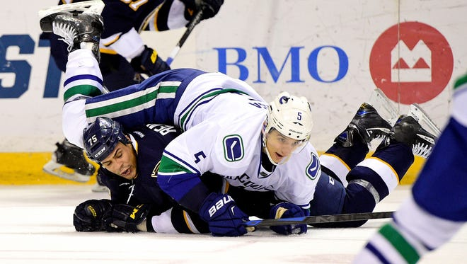 Vancouver Canucks defenseman Luca Sbisa (5) tackles St. Louis Blues right wing Ryan Reaves (75) during the second period at Scottrade Center.