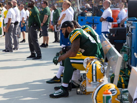 Green Bay Packers tight ends Lance Kendricks (84) and Martellus Bennett (80) sit on the bench during the national anthem prior to the game against the Cincinnati Bengals at Lambeau Field.