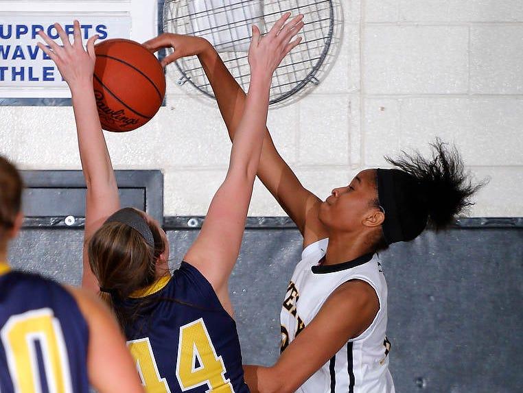 Waverly's Alisia Smith, right, blocks a shot by DeWitt's Lilly George Friday, Feb. 6, 2015, at Waverly High School.