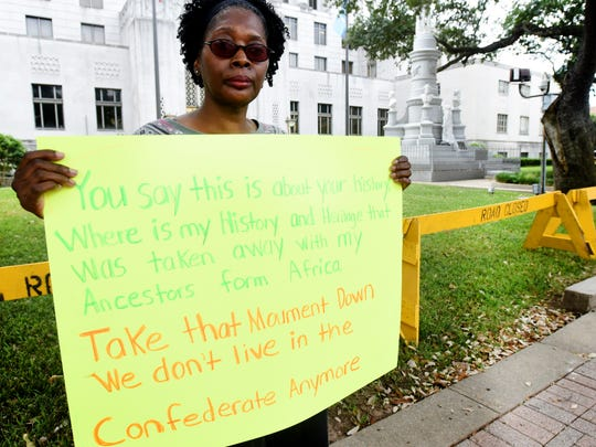Barbara Maxey holds a sign to protest the GULF Coast Patriot Network 'Rally To Be United As One' event Saturday morning at the Caddo Parish Courthouse.