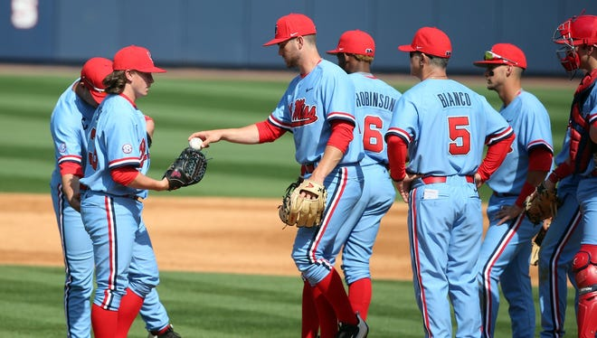 Starting pitcher Andy Pagnozzi (middle) hands the ball to closer Wyatt Short (left) during Saturday's 4-0 loss to South Carolina. Ole Miss' starting pitchers posted an 8.03 ERA over 12 1/3 innings.