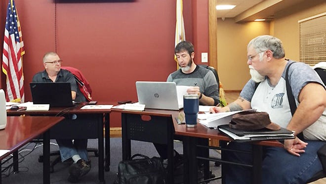 Commissioner Kyle Buchanan, middle, speaks as Mayor Chris Wilder, left, and Commissioner Dwayne Price listen during the Chenoa City Council meeting Tuesday. The meeting was held in person with a limited number allowed, and on Zoom.