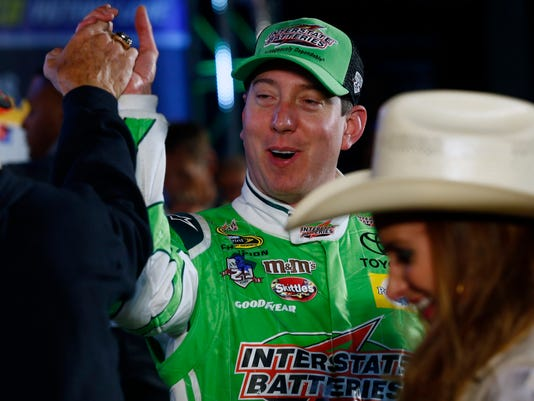 Kyle Busch (18) celebrates winning the NASCAR Sprint Cup Series auto race at Texas Motor Speedway in Fort Worth, Texas, Sunday, April 10, 2016. (AP Photo/Ralph Lauer)