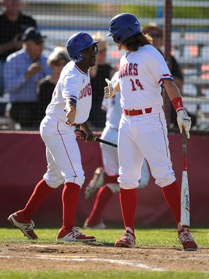 Cooper's Terreon Paige (5) is congratulated by teammate Zach Goodson (14) after scoring a run in the bottom of the third inning of the Cougars' 11-3 win on Friday, April 7, 2017, at Cooper High School.