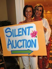 Andrea Baker and event co-chair Brenda Woolston encouraged guests to check out the silent auction.