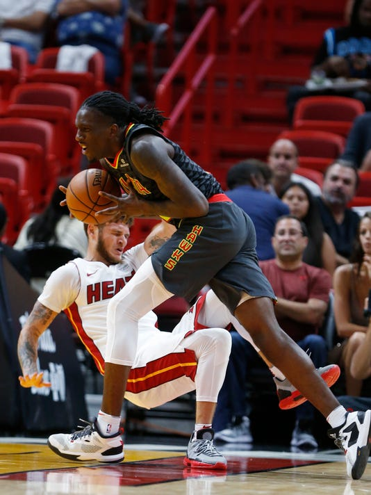 Atlanta Hawks forward Taurean Prince, right, fouls Miami Heat guard Tyler Johnson as he goes up for a shot during the first half of an NBA preseason basketball game, Sunday, Oct. 1, 2017, in Miami. (AP Photo/Wilfredo Lee)