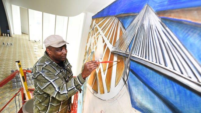 Award-winning artist Hubert Massey works on his vast fresco at Cobo Center in Detroit on Friday.