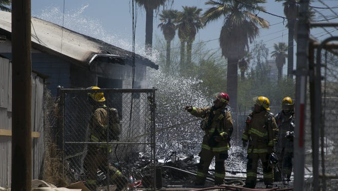 Firefighters work to put out a structure fire near 22nd avenue and Madison street on Thur. May. 17, 2018 in Phoenix, Ariz.