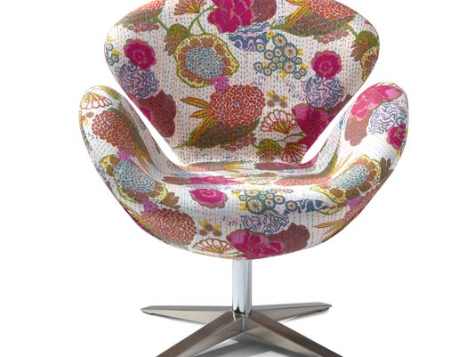 A contemporary bucket chair with a vibrant floral print