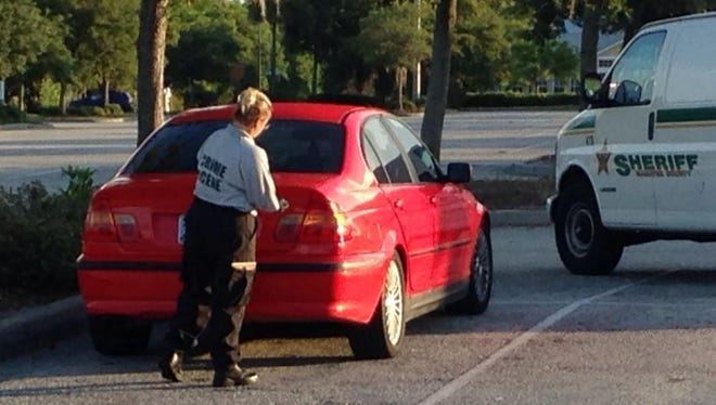 A Manatee County Sheriff's crime scene investigator dusts a red BMW for fingerprints July 28, 2014, at Royal Palm Theater in Bradenton, Fla.