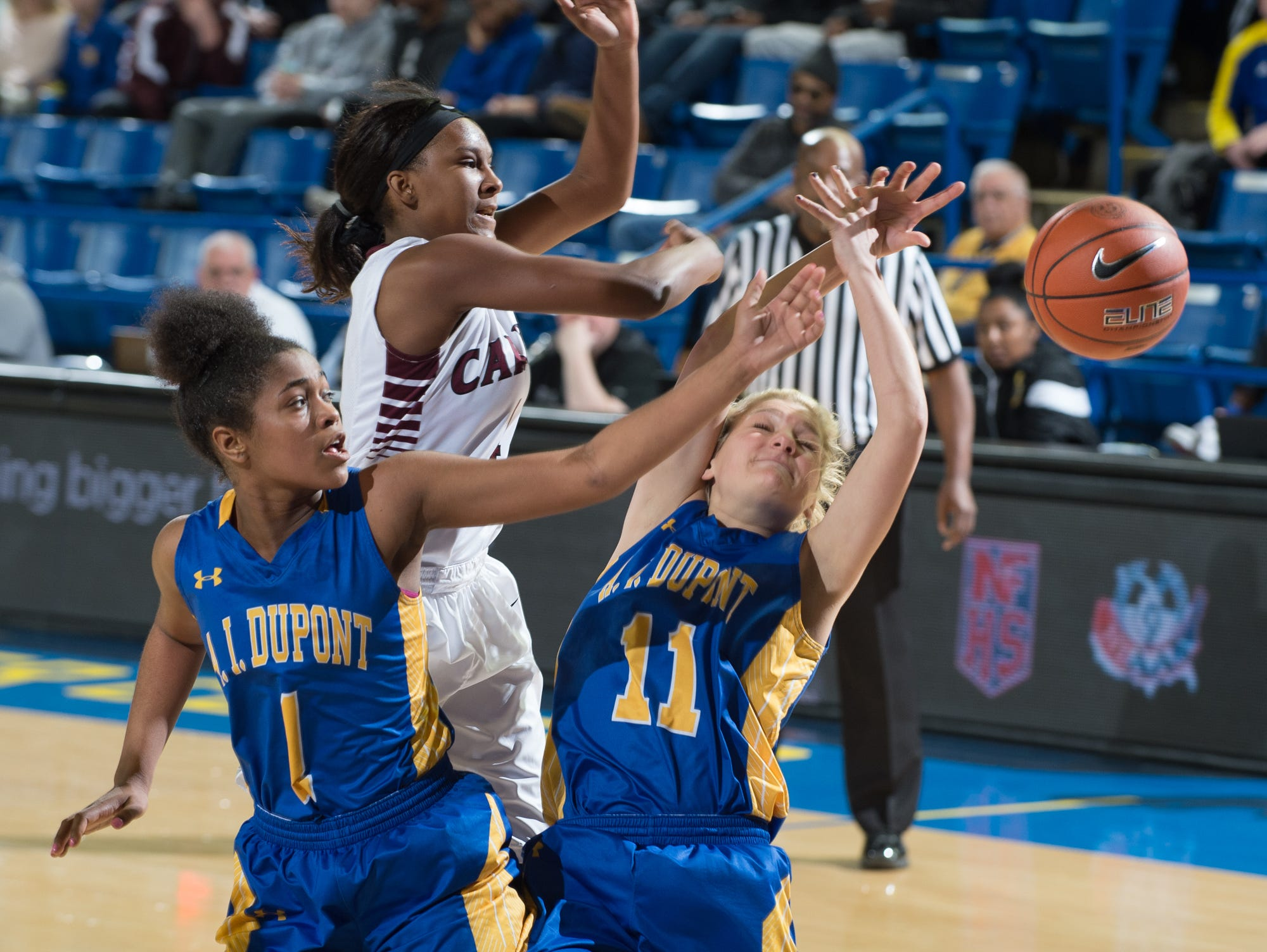 Caravel's Sasha Marvel (4), A.I. duPont's Alexandria Ferrell (1) and teammate Sydney MacDonald (11) go for a loose ball in the quarterfinals of DIAA Girls Basketball Tournament at the University of Delaware.