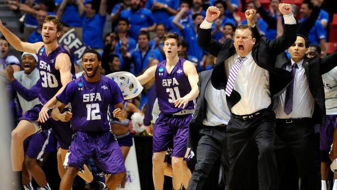 Stephen F. Austin Lumberjacks head coach Danny Kaspar celebrates with his players after defeating the VCU Rams in a men's college basketball game during the second round of the 2014 NCAA Tournament at Viejas Arena.