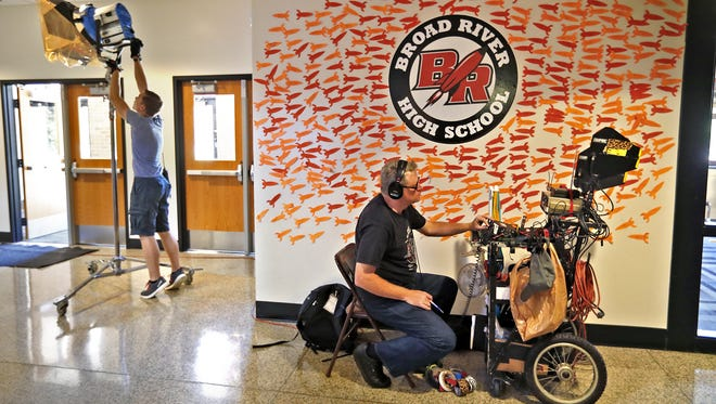 """Crews, including TJ Caroway, left, and D. Brad Bryan, get set at the filming set of the Duplass Bros. movie, """"The Miseducation of Bindu,"""" Tuesday, July 17, 2018, at the old Broad Ripple High School.  The old school logo has been changed to """"Broad River High School,"""" for the film."""