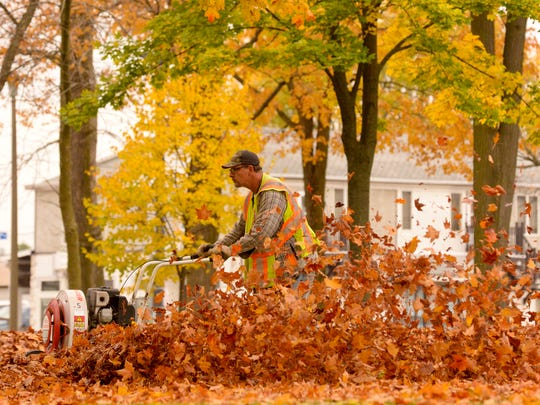 Dave Reilly, from the City of Manitowoc Parks and Recreation Department, uses an eight-horse walk-behind blower to clear fallen autumn leaves from Washington Park in Manitowoc in October 2014.