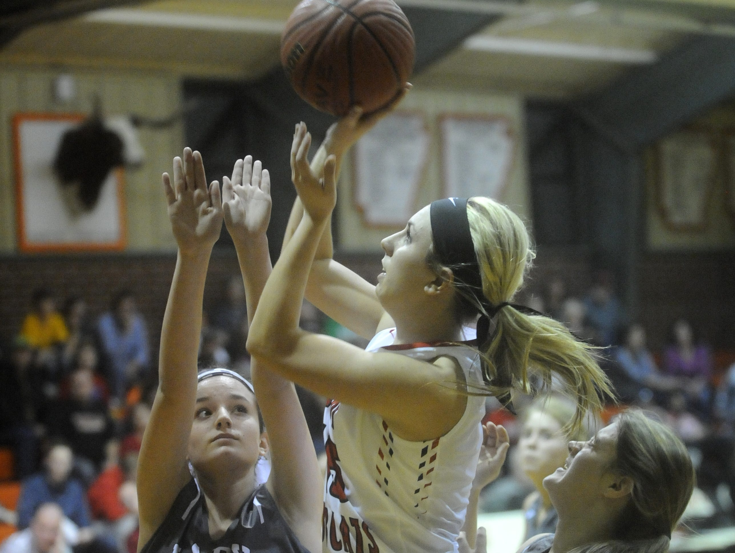 Flippin's Sydney Riggs shoots over Izard County's Harley Thomason (12) during the Lady Bobcats' 56-31 loss to the Lady Cougars.
