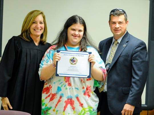 Magistrate Judge Carol Whitehearst and Deputy US Marshal Michael Dicharry present Junior Deputy Marshall certificate to Elizabeth Brown.
