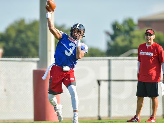 UL quarterback Jordan Davis works on the opening day of training last Wednesday under the watchful eye of Cajuns coordinator Jorge Munoz.