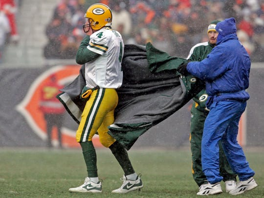 Former Green Bay Packers quarterback Brett Favre holds a hand warmer to his face as he gets rid of a long jacket in the second half against the Chicago Bears on Dec. 23, 2007, at Soldier Field.