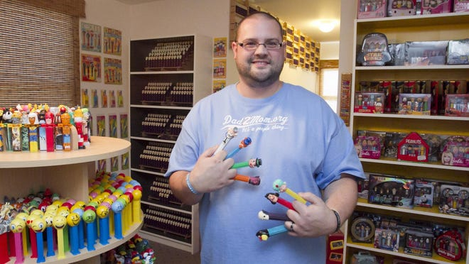 Jim Blaine holds several of his more rare PEZ dispensers.