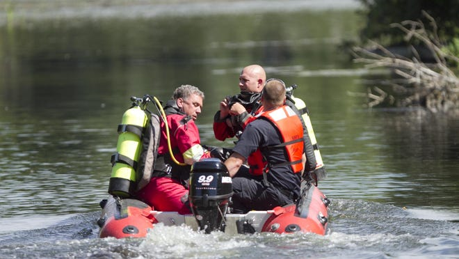 The Livingston County Sheriff's Department Dive Team launches at a boat launch on Handy Lake in Hartland Township, heading out to search for an 18-year-old boy whose body was later recovered after a 71-minute search.