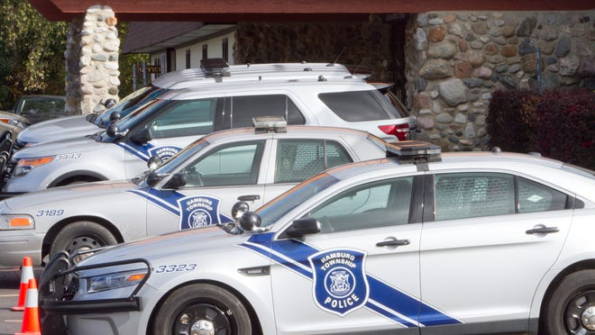Hamburg Township Police Department vehicles fill parking spots along the front of Borek Jennings Funeral Home in Hamburg Township as viewing of Sgt. James Sanderson began Wednesday. Sanderson, 46, died Friday.