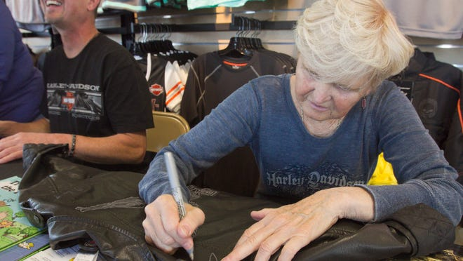 Jean Davidson, right, a member of the founding Davidson family of Harley-Davidson fame, signs the leather jacket of 4-year-old Isaac Dziedzic, while his grandmother Lynette Dziedzic talks off-camera with Jean's son Jon, left. The Davidsons were at an event at Brighton Harley-Davidson signing copies of several of Jean's books as well as T-shirts and even occasionally bikes.