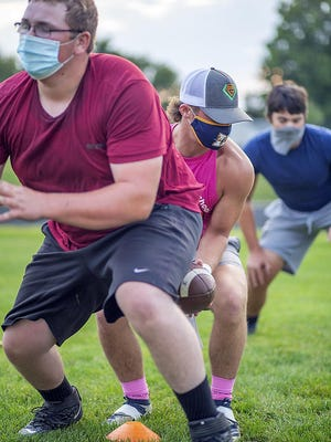 Knoxville High School juniors, from left, Matt Cummings, Bryar Fleisher and Garrett Larson run an offensive play during football workouts on Thursday, Sept. 24, at Dennis Larson Field.
