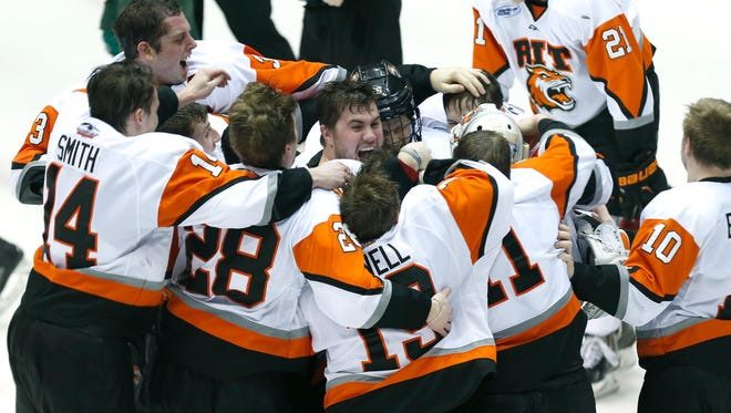 RIT's Greg Amlong, center, celebrates with his teammates after the TIgers' 5-1 win over Mercyhurst in the in the Atlantic Hockey championship at the Blue Cross Arena at the War Memorial in Rochester on Saturday, March 21, 2015.