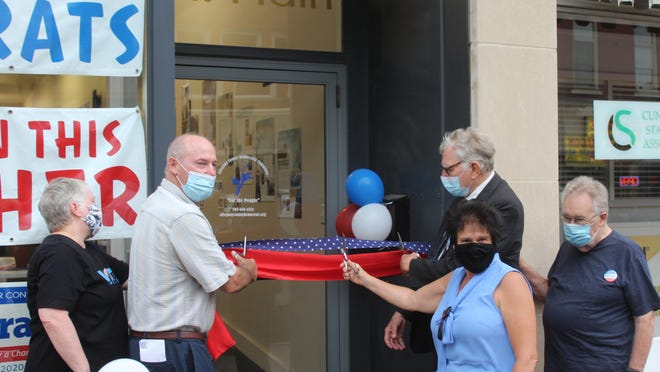 Allegany County Democratic Committee Chairman Mike McCormick, congressional candidate Tracy Mitrano, assembly candidate Ross Scott and party supporters cut the ribbon on election headquarters in Wellsville Thursday night.
