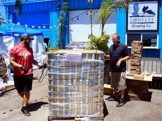 Josh LaSalle (left) and Aaron Hanson move empty cans of Khryseis Blonde Ale as they prepare for their grand opening and sale Thursday, July 27, 2017, at Lorelei Brewery in Corpus Christi. Lorelei Brewing Co is releasing its very first craft beer canned in Corpus Christi.