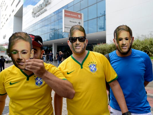 Supporters wear soccer star Neymar face masks as they pose for a photo at the Mater Dei Hospital, in Belo Horizonte, Brazil, Saturday, March 3, 2018. Neymar will have surgery on a fractured toe in his right foot and could be out for up to three months, an estimate that would take the Brazil striker right up to the World Cup. Neymar was injured Sunday in Paris Saint-Germain's match against Marseille in the French league (AP Photo/Eugenio Savio)