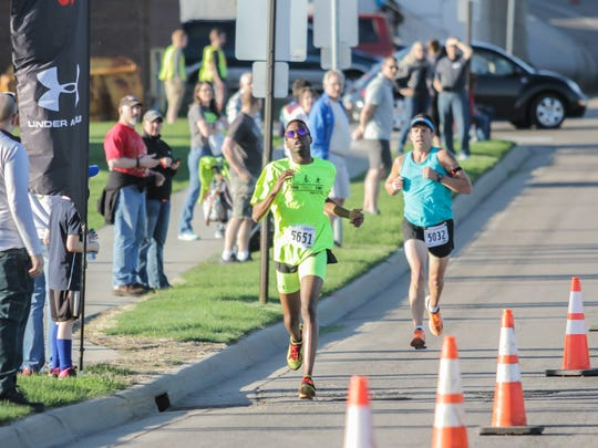 Morcelli Kombo (neon) runs on his way to the Earth Day 5K title in 2017. He has finished in the top five of the event each of the last five years.